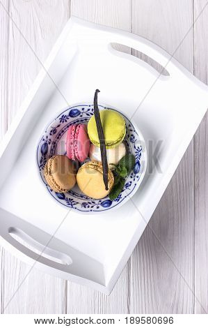 Colored macarons, mint and vanilla bean on a white wooden background. Top view