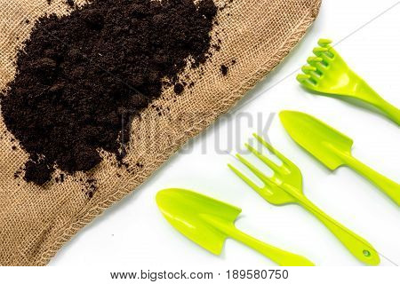 green equipment with rake, trowel, ground for planting greenary in summer on white desk background top view