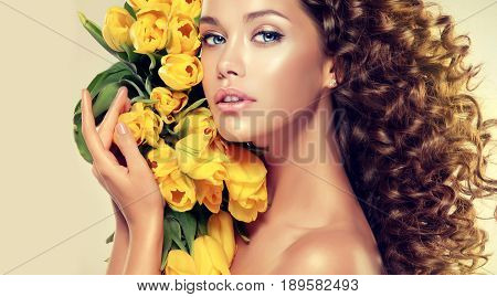 Beautiful model girl with long curly brown hair . Young brunette woman holding yellow tulips . Girl summer . Girl spring