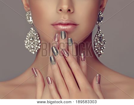 Beautiful model girl with pink and silver  metallic manicure on nails . Fashion makeup and cosmetics . Big silver diamond Shine  earrings jewelry .