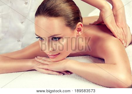 Massage and body  care. Spa body massage treatment. Woman having massage in the spa salon for beautiful girl