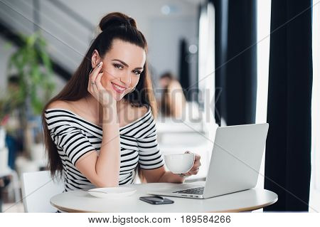 Adult attractive businesswoman is working on her laptop in a cafe, smiling young woman is using a laptop in sidewalk cafe, smiling girl with laptop computer in cafe