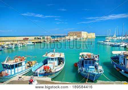 CRETE ISLAND, GREECE, SEP 12, 2012: View on beautiful classic old piscatory small sea boats ships, white yachts, Heraklion Greek sea port, tourists, and blue water of Aegean Sea bay. MSC cruises