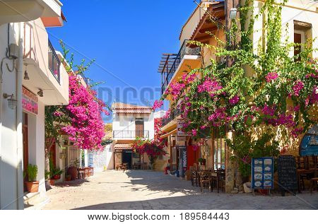 CRETE ISLAND, GREECE, SEP 06, 2012: View on Panormo small city street with bakery restaurant cafe red flowers small hotel for tourists guests Greece islands holidays vacations famous sightseeing tours