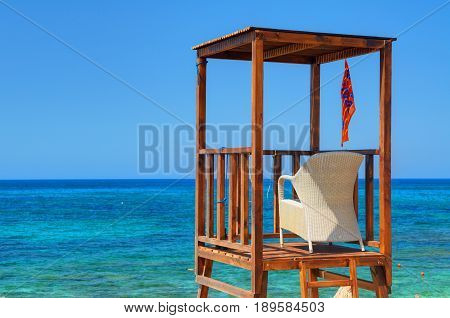 View on wooden beach rescue man place house cabin tower lifeguard on blue sea sand. Rescuer loge chair and flag. Mediterranean Sea, tropical holidays vacations tours