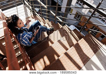 Dreamful mulatto girl is listening to music form earphones while sitting on steps. She is holding cellphone and looking forward pensively. Top view