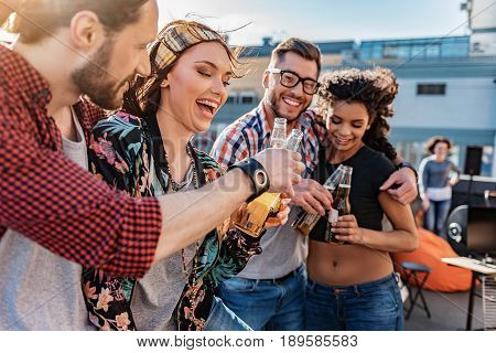 Happy young man and woman are clinking glass bottles on beer while hugging. They are smiling. Loving couple is standing near them on rooftop terrace