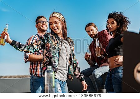 Low angle of sexy girls dancing on rooftop terrace with enjoyment. Guys are looking at them and smiling. They are drinking beer