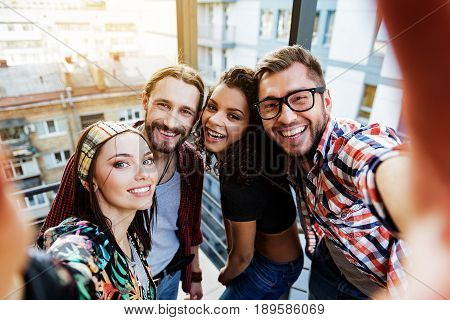 Portrait of cheerful four friends making selfie while hanging out on stairs. They are looking forward and smiling