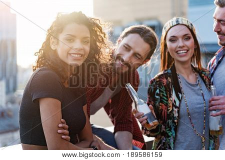 Portrait of excited mulatto girl having fun with her friends on roof. They are looking at camera and laughing while drinking beer