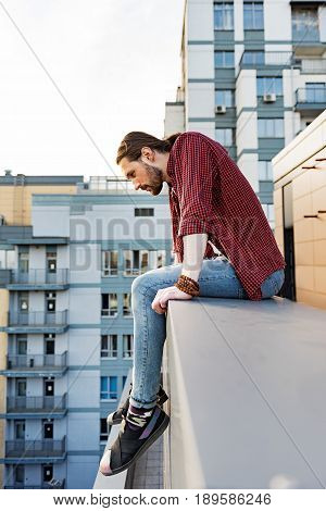 Calm young man is sitting on border of roof and looking down with interest
