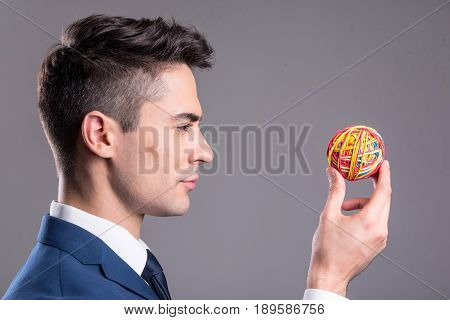 Side view cheerful male watching at small colorful ball while holding it in hand. Enthusiasm concept
