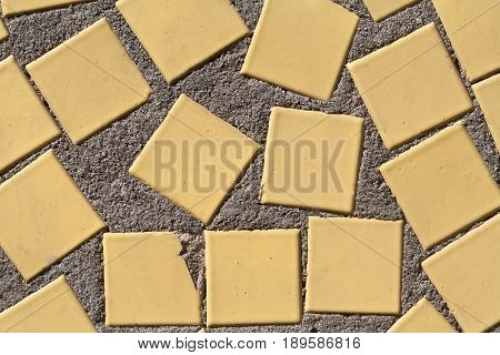 The facade of a residential building. The old wall. It is enclosed with a shallow square tile. Abstraction