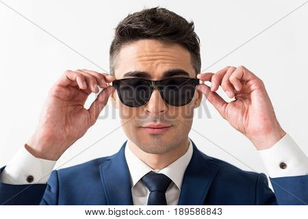 I am so cool. Portrait of cheerful handsome young male trying on sunglasses while watching at camera. Confidence concept