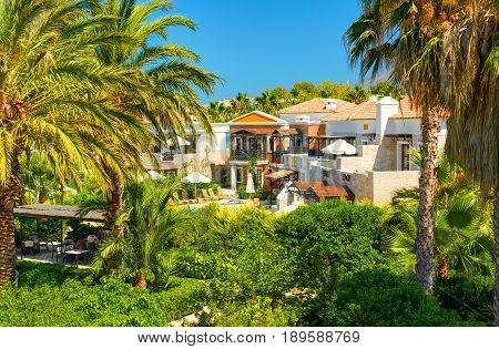 CRETE ISLAND, GREECE, JULY 01, 2011: View on hotel villas for tourists guests. Green tropical palm trees swimming pool, sun beds, umbrellas. Classic architecture. Greece island holidays tours