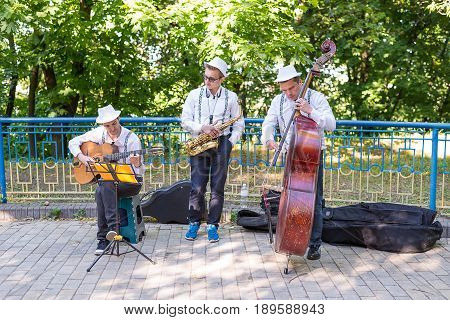 KIEV UKRAINE - June 04 2017. Street musicians: guitarist saxophonist and bass player play on the street