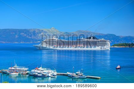 CORFU ISLAND, GREECE, JUN,06, 2014: Giant amazing white touristic passenger liner vip yachts in Ionian Sea. MSC FANTASIA cruise liners. Greece islands holidays tours Mediterranean Sea cruises