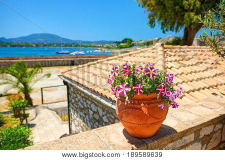 Clay jug with magenta flowers on stone wall. Classical yachts in Mediterranean sea. Kerkyra castle. Greece holidays vacations tours famous sightseeing. Greek antique flowers jug vase. Blue sea