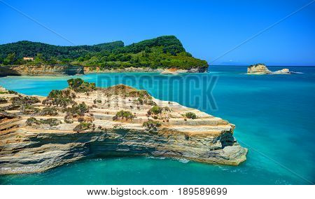 Beautiful view on Corfu island green hills mountains and sand seamy rocks and swimming people in the Ionian blue sea. Sand hill rocks. Greece holidays vacation tourist tour. Sightseeing view point