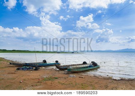 Fishing boat on Shore or Beach beside lake pond under blue sky on Sunny Day