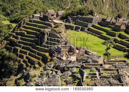 Closeup view of the Lost Incan City of Machu Picchu near Cusco Peru. Machu Picchu is a Peruvian Historical Sanctuary. People can be seen on foreground.