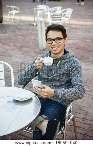 Young asian man sitting and smiling in relaxing outdoor cafe holding cup of coffee and messaging on mobile phone