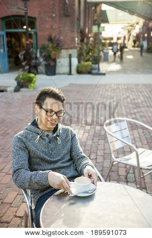 Young asian man sitting and smiling in relaxing outdoor cafe holding cup of coffee looking down