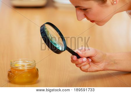Woman Inspecting Honey With Magnifying Glass.