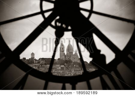 Sacre-Coeur viewed through Giant clock tower in Paris, France.