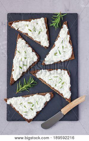 Pumpernickel bread with feta cream cheese rosemary lemon and garlic dip on slate board top view vertical