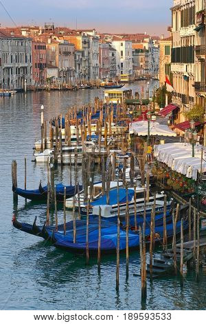 Venice, Italy, May, 31, 2017: landscape with the image of boats and gondolas on a channel  at sunrise in Venice, Italy