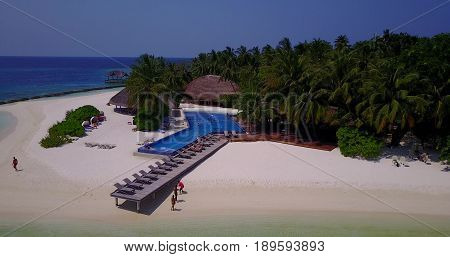 Aerial flying drone view of Maldives white sandy beach swimming pool in luxury 5 star resort hotel relaxing holiday vacation on sunny tropical paradise island with aqua blue sky sea ocean 4k.
