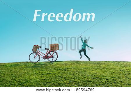 Alone asian Woman and bicycle Jumping for Joy on a Grass Hill above horizon line One happy slim girl fly in a green field against blue summer sky with clouds and text of freedom