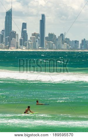Two Surfers In Water With Gold Coast Cityscape On Background