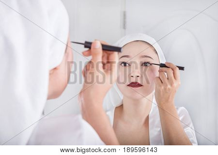 Woman Looking Mirror And Make-up With Black Eyeliner