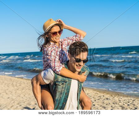 young funny couple in sunglasses piggybacking on the beach. Sea is on background. Girl is wearing hat.