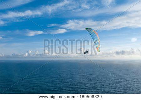 Danger extreme flying tandem paraglider over the sea.