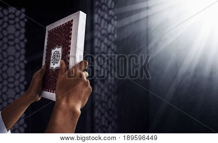 Muslim man hands holding koran in mosque