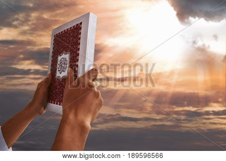 Muslim man hands holding koran with sky background