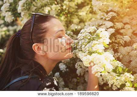 Happy Brunet Sniffs White Flowers