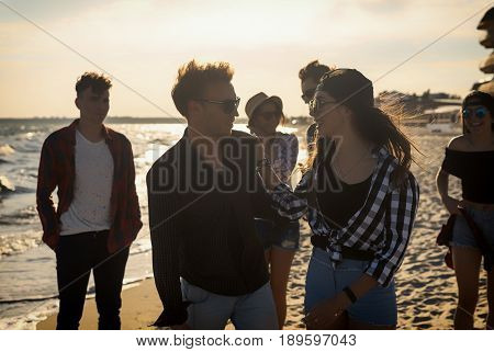Group of young friends on the beach together. frienship concept. Sunset time