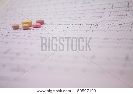 Background of a three-channel holter electrocardiogram of a patient with cardiac pacemaker and five colored pills