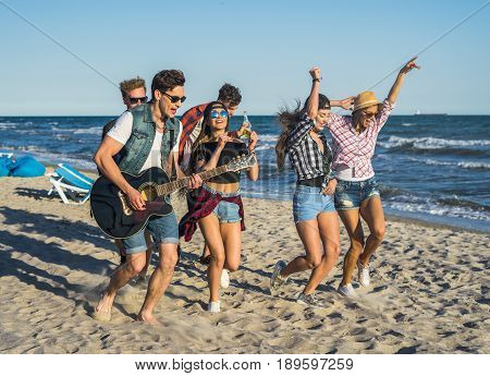 Party on the beach with guitar. Friends dancing together at the beach. Happy youth time. Girls dancing with hands up