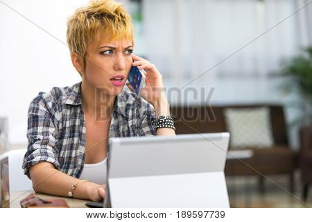 Perplexed Young Woman Talking On Her Mobile Phone