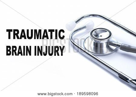 Page with TRAUMATIC BRAIN INJURY on the table with stethoscope medical concept.