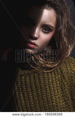model girl with wet hairsyle, tests portrait over white background, half face in the shadow