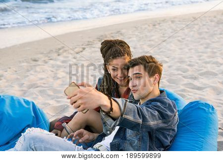 young couple taking selfie photo at the beach. Handsome man and pretty girl with zizi cornrows dreadlocks
