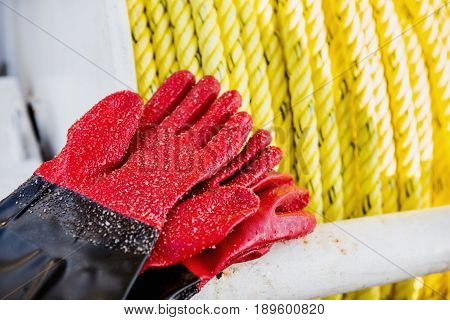 Fishing gloves covered with sand lie on fishing boat.
