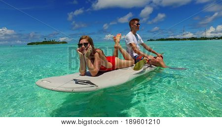 Maldives white sandy beach 2 people young couple man woman paddleboard rowing on sunny tropical paradise island with aqua blue sky sea water ocean