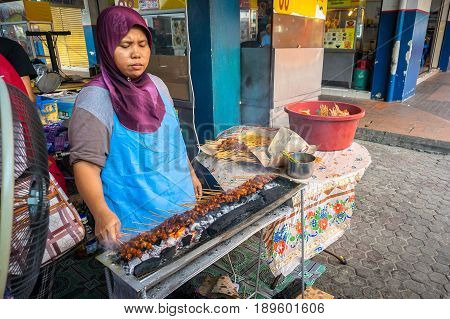 Kota Kinabalu,Sabah,Malaysia-May 28,2017:Street local preparing delicious barbecue chicken & beef satay on charcoal in Kota Kinabalu,Sabah.Sabah is the most popular food capitals in Malaysia